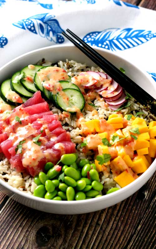 An absolutely divine Hawaiian Tuna Poke Bowl with fresh ahi tuna, bright crisp radish, cucumber, edamame, and sweet mango over wild rice with a drizzle of sweet chili aioli? Yes, please!